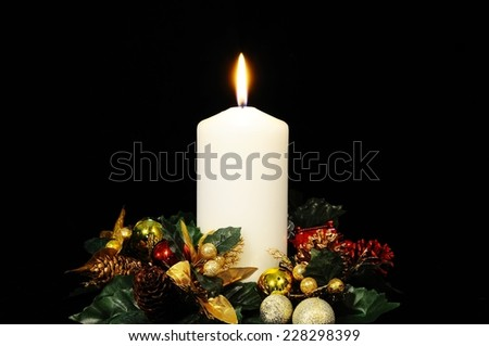 White candle and Christmas flowers against a black background. - stock photo