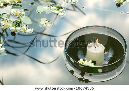white candle in glass floating in water reflecting sky and flowers of jasmin - stock photo