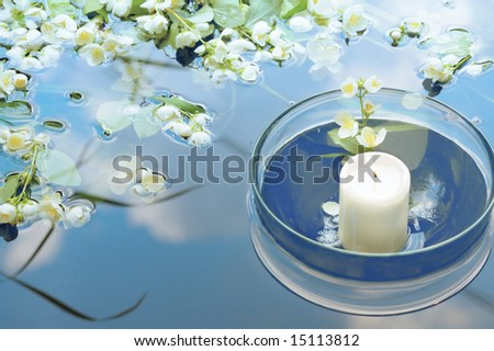 white candle in glass floating in water with jasmin reflecting sky - stock photo