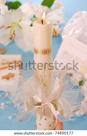 white candle with decoration for first holy communion on blue background - stock photo