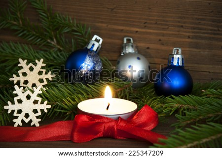 White Candle with Red Bow and Christmas or Winter Decoration, Background for Winter Season with Wood, Snowflakes, Christmas Balls and Fir Tree Branches - stock photo