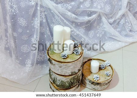 White candles and cones lie on the parts of birch trunk - stock photo