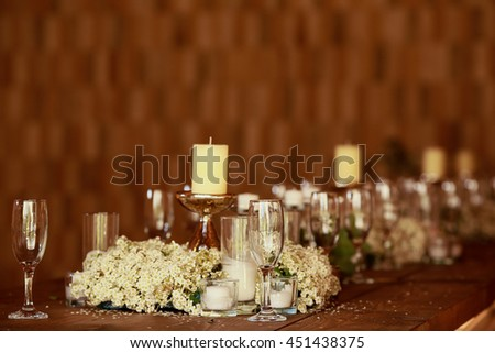 White candles stand on the steel holders among beautiful white flowers - stock photo