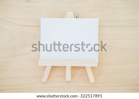 White canvas art board on wood texture background - stock photo