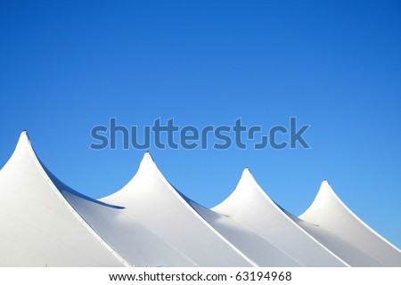 White canvas event tents against blue sky. - stock photo