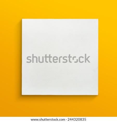 White canvas frame on yellow wall background. - stock photo