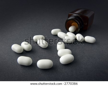 white caplets spilling from brown bottle; dramatic lighting - stock photo