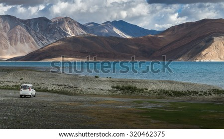 White car at Pangong lake with beauty view surrounded by mountain range and turquoise colour lake.   - stock photo