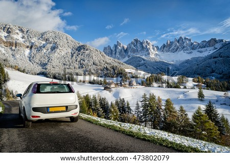 White car on a road trip in a Dolomites landscape in winter with snow on the trees, the Geisler mountains and the church of the village St. Magdalena in the Villnoesstal (Val di Funes valley), Italy.