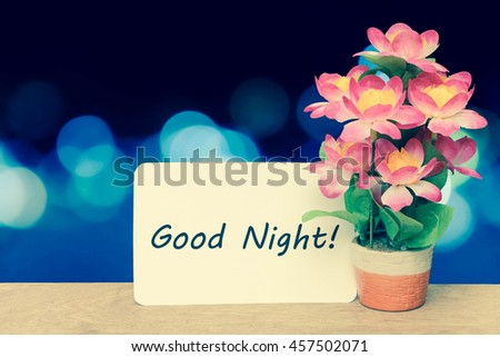 white card and flower vase on blur bokeh light in city in blue tone - stock photo