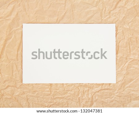White card on packing paper. Background - stock photo