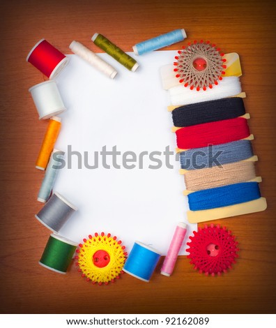 White card on the table with sewing threads around the card. - stock photo