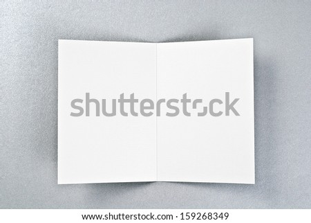 White card or sheet of paper over silver background - stock photo