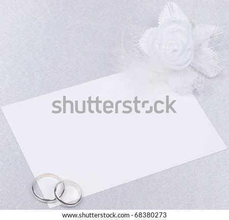 White card, wedding rings, flowers from silk on a background from  silk