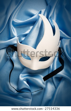 white carnival mask on blue silk - stock photo