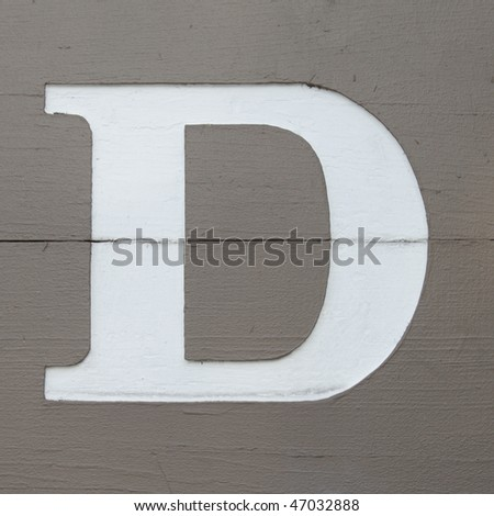 White carved letter d on the wooden board