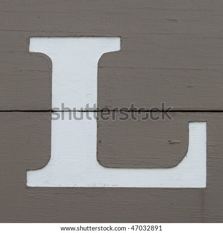White carved letter l on the wooden board