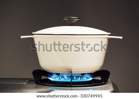 white cast iron saucepan on the gas stove - stock photo