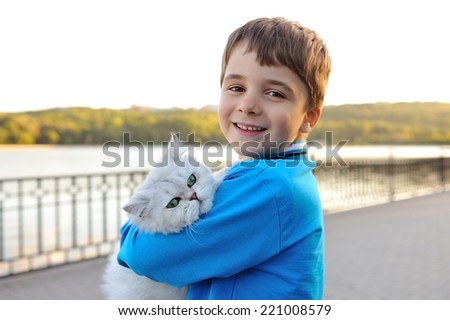 White cat sitting on hands of a boy. - stock photo