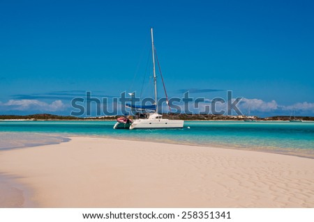 White Catamaran sailboat anchored or moored in the turquoise tropical waters with white sand beach in the foreground - stock photo