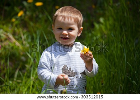 White caucasian baby boy holds yellow dandelion in hand smiling outdoors in the green meadow, Aosta valley, Italy - stock photo