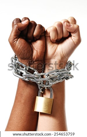 white Caucasian hand chained with iron chain and locked together with black ethnicity female around wrists in togetherness, multiracial respect and understanding concept isolated on white background - stock photo