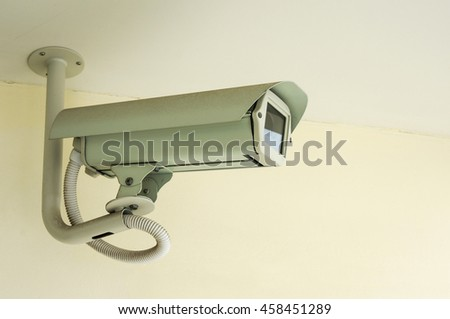 White CCTV security camera on ceiling background ,Closed-circuit television record activity peoples in office and walkway