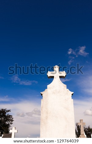 White cemetery cross against blue sky with copy space. - stock photo