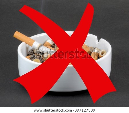 White ceramic ashtray full of smokes cigarettes with red prohibition sign. Campaign against smoking concept.