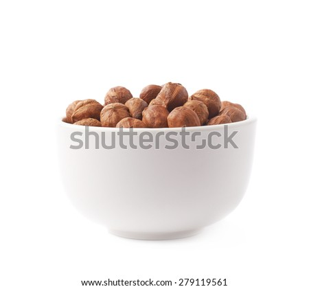 White ceramic cup bowl filled with the multiple hazelnuts isolated over the white background - stock photo
