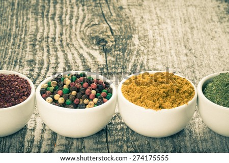 White ceramic cups with different kinds of spices on old wooden board. Selective focus. Toned. - stock photo