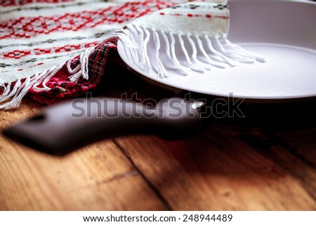 White ceramic pan with a black pen on the old wooden table with a towel. - stock photo
