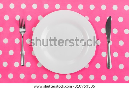White ceramic plate, metal fork and knife on the table, a bright pink tablecloth with white polka dots. Concept of food choice, diet, weight loss, lifestyle. Breakfast, lunch, dinner. - stock photo