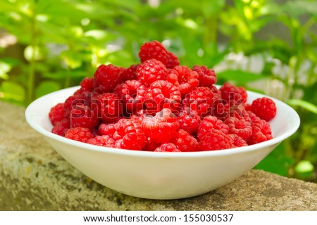 White ceramic plate up to the top filled with berries ripe raspberry lies on a stone slab