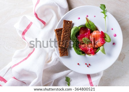 White ceramic plate with Sliced salmon filet, salted with beetroot juice, served with whole wheat toasts, salad leaves and beetroot sauce over white marble surface with white textile.Top view - stock photo