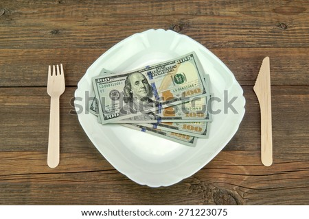 White Ceramic Plate With USA New One Hundred Dollar Bills, Wooden Fork And Knife On Rough Wood Background Or Texture - stock photo