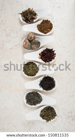 White Ceramic Sample Spoons with Various Black and Green Teas  - stock photo