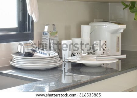 White ceramic set and stainless kitchen utensils on the counter - stock photo