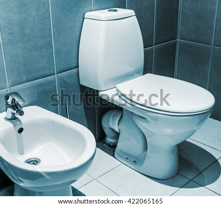 white ceramic toilet in tiled bathroom. Focus on the edge of the toilet bowl. toned image - stock photo