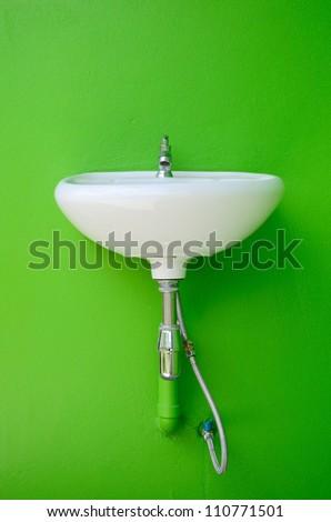 White ceramic washing sink on green wall. - stock photo