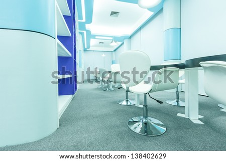 white chair and tables set for reading with ceiling lamp in the empty modern library - stock photo