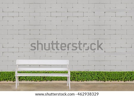 white chair  at green bush fence and concrete floor on white brick wall background