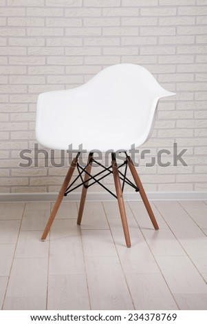 White chair on a brick wall background - stock photo
