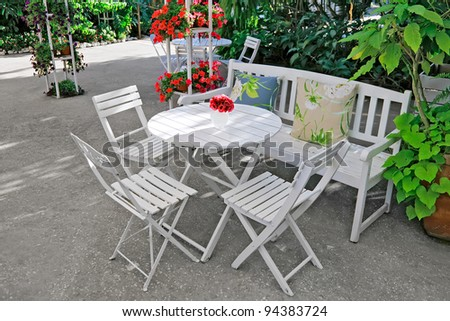 White chair, table, bench with pillows in a lush garden. - stock photo