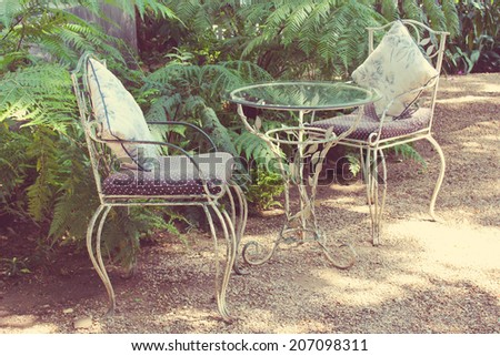 White chair, table, bench with pillows in garden. - stock photo