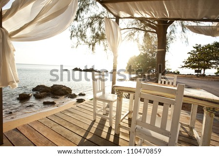 White chairs and table on a balcony with nice view to the sea - stock photo