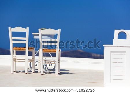 White chairs and table overlooking spectacular caldera surrounding beautiful island of Santorini, Greece - stock photo