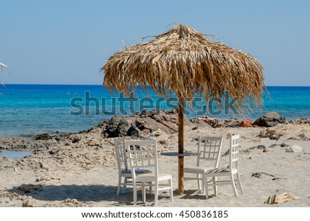 white chairs and table with a beautiful view of tropical turquoise ocean under a straw umbrella - stock photo