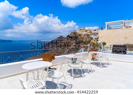 White chairs on terrace and beautiful view of Firostefani village on cliff, Santorini island, Greece.