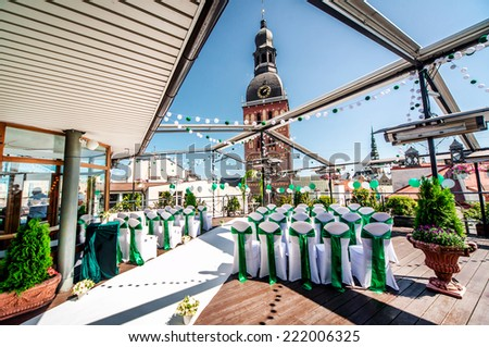 White chairs with green ribbon on a terrace is ready for a wedding ceremony  - stock photo